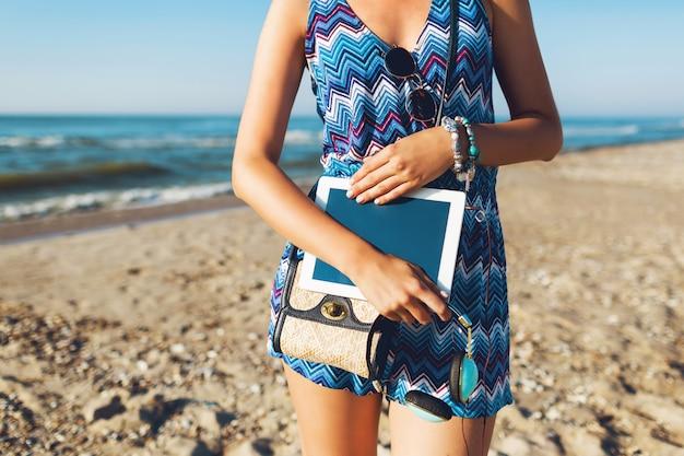 Stilvolle frau, die tablette hält und auf tropischem strand geht