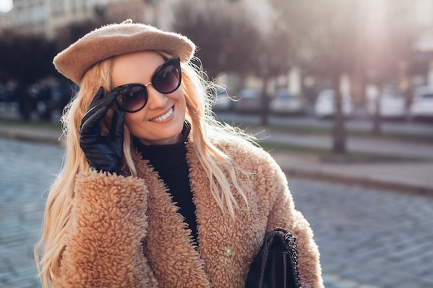 Stilvolle frau, die teddymantel-baskenmützen-sonnenbrille trägt und geldbörse im freien hält