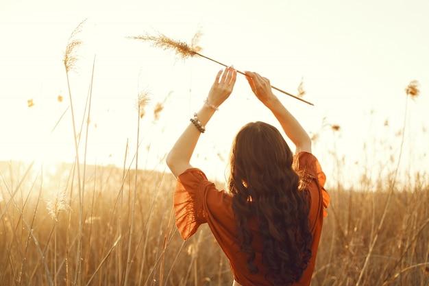 Stilvolle frau, die zeit in einem sommerfeld verbringt