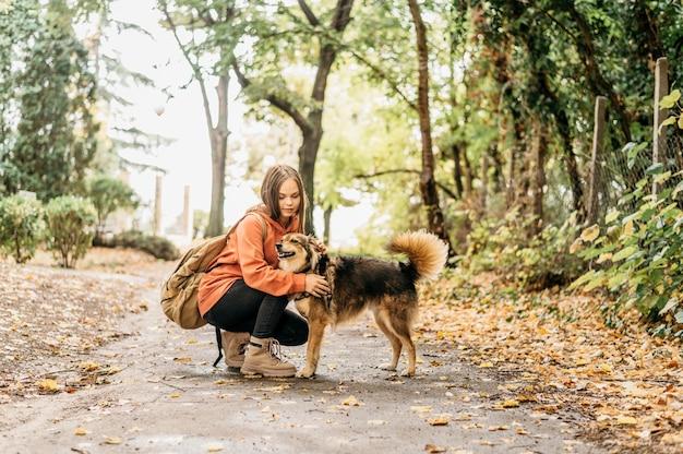 Stilvolle frau für einen spaziergang mit ihrem hund