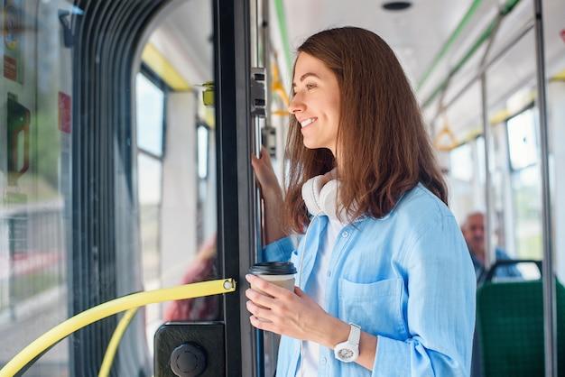 Stilvolle frau im blauen hemd, die reise in der modernen straßenbahn oder im bus genießt, steht mit tasse kaffee im öffentlichen verkehr.