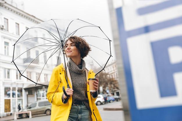 Stilvolle frau im gelben regenmantel gehend durch stadtgebiet unter dem großen transparenten regenschirm, der in der hand mitnehmerkaffee hält