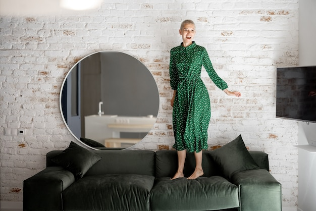 Stilvolle frau im grünen kleid, die auf einer couch im wohnzimmer springt. unbeschwerter lebensstil und wohnkomfort-konzept