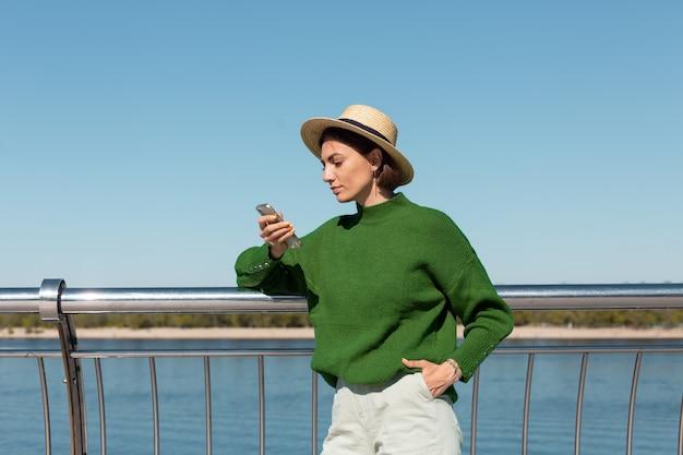 Stilvolle frau im grünen lässigen pullover und hut im freien auf brücke mit blick auf den fluss am warmen sonnigen sommertag halten handy-lächeln