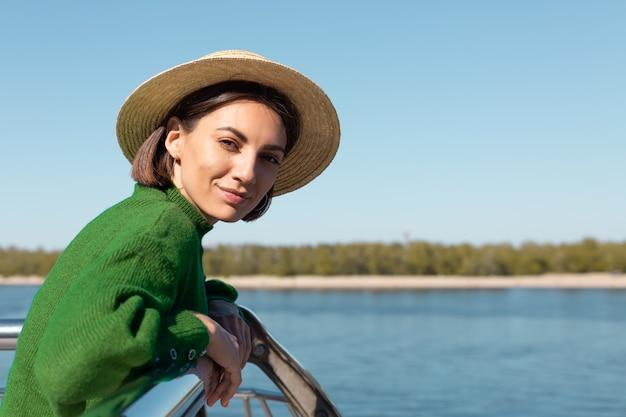 Stilvolle frau im grünen lässigen pullover und hut im freien auf brücke mit flussblick genießt sommerlichen sonnigen tag