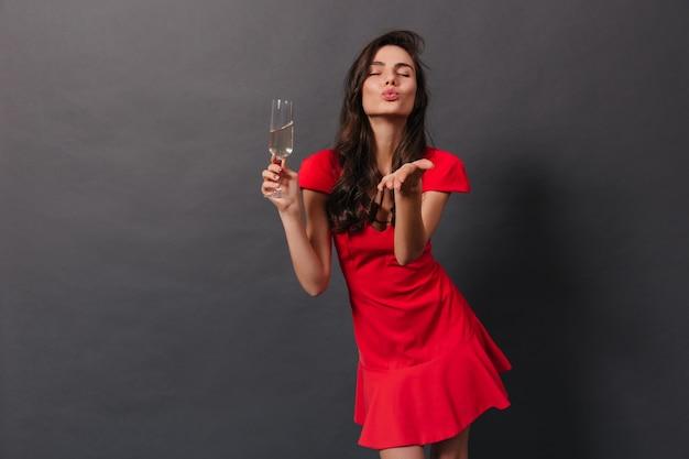 Stilvolle frau im hellen kleid, die kuss sendet und glas sekt auf schwarzem hintergrund hält.