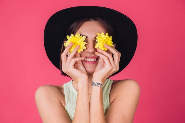 Stilvolle frau im hut, lächeln auf gesichtsbedeckungsaugen mit gelben astern, frühlingsstimmung, glückliche gefühle isolierten raum