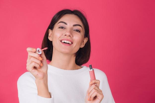 Stilvolle frau im lässigen weißen pullover auf rosa roter wand