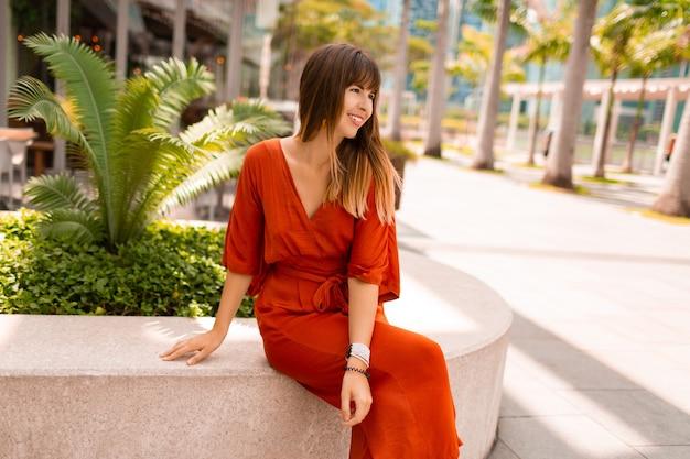 Stilvolle frau im orangefarbenen kleid, das auf promenade mit palmen und wolkenkratzern in der großen modernen stadt aufwirft