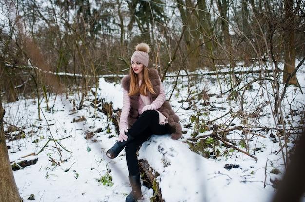 Stilvolle frau im pelzmantel und im headwear am winterwald.
