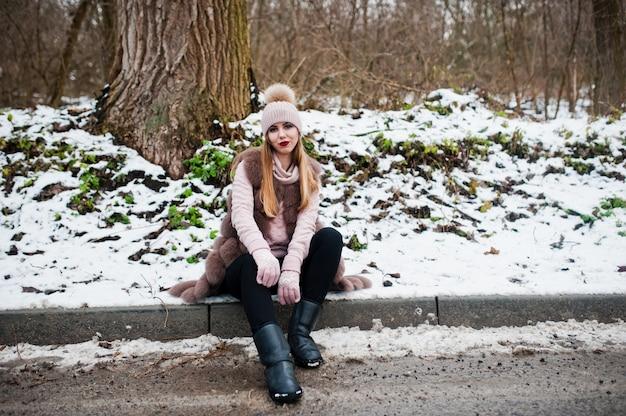 Stilvolle frau im pelzmantel und in der kopfbedeckung am wintertag auf sitzendem rand ofroad.
