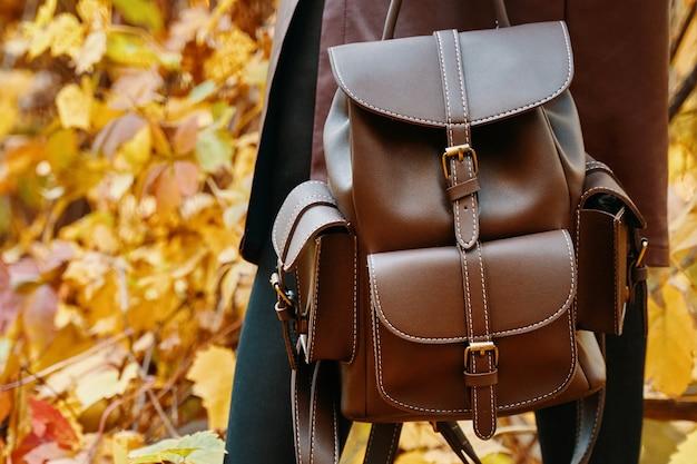 Stilvolle frau im rock und mit rucksack herbstspaziergang im park herbstlaub im hintergrund na...