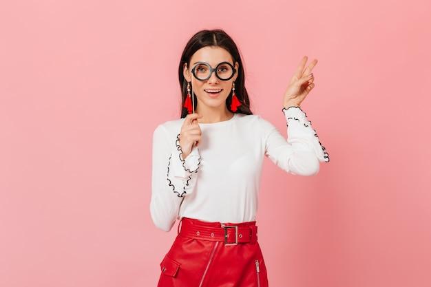 Stilvolle frau im roten lederrock und in den hellen ohrringen zeigt friedenszeichen auf rosa hintergrund. porträt des mädchens in runden brillen.