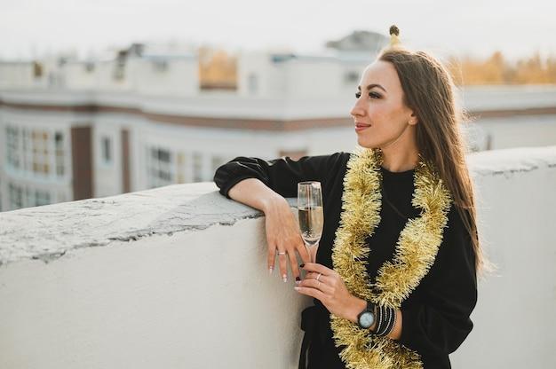 Stilvolle frau im schwarzen kleid mit einem glas champagner