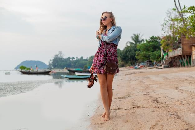 Stilvolle frau im sommerkleidurlaub, der am strand mit schuhen in der hand geht
