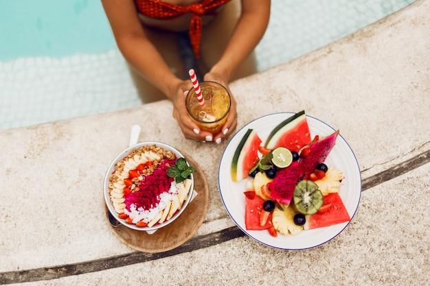 Stilvolle frau im tropischen outfit, die vegetarisches essen genießt. smoothie-schüssel, obstteller und limonade. draufsicht.
