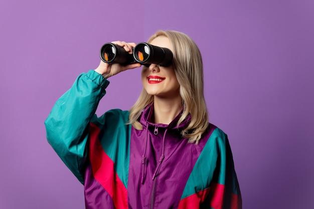 Stilvolle frau in 80er windjacke und roud sonnenbrille hält fernglas auf lila wand