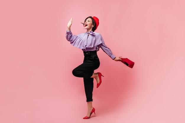 Stilvolle frau in bluse mit volants und roter baskenmütze hält tasche und winkt hand mit lächeln.