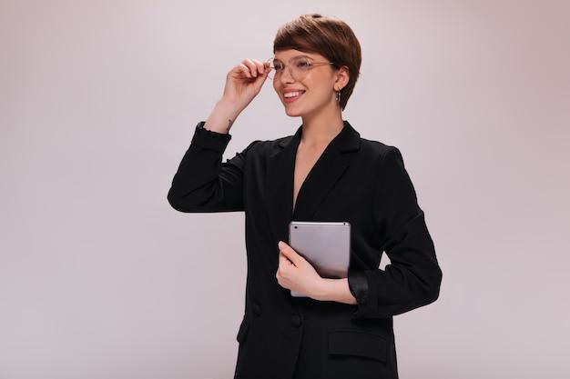 Stilvolle frau in brillen, die tablette lächeln und halten. charmante dame im schwarzen anzug wirft in guter laune auf lokalisiertem hintergrund auf
