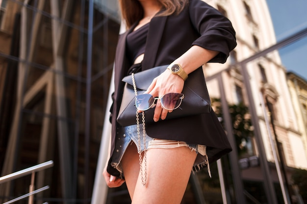 Stilvolle frau in der schönen kleidung hält eine tasche und okulare in der hand