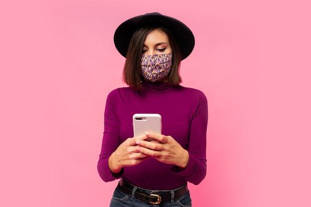Stilvolle frau in der schutzmaske und im schwarzen hut unter verwendung des mobiltelefons, stehend.