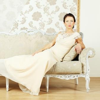 Stilvolle frau in einem abendkleid in einem luxuriösen interieur