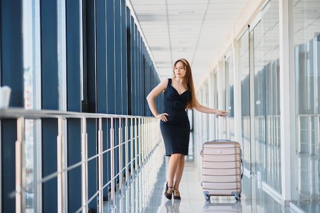 Stilvolle frau in einem schwarzen kleid mit einem koffer im flughafenterminal, der auf ein flugzeug wartet