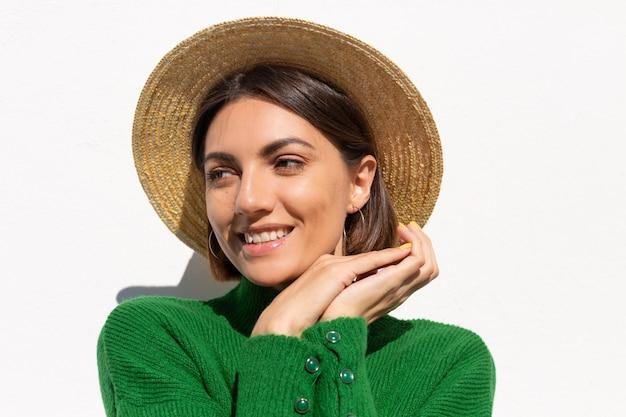 Stilvolle frau in grünem lässigem pullover und hut im freien auf ruhigem und selbstbewusstem lächeln der weißen wand