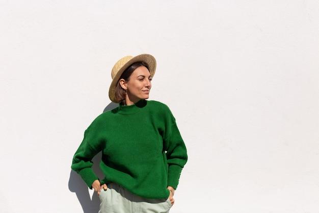 Stilvolle frau in grünem lässigem pullover und hut im freien auf weißer wand fröhlich, freudig und aufgeregt genießt heißen sommertag