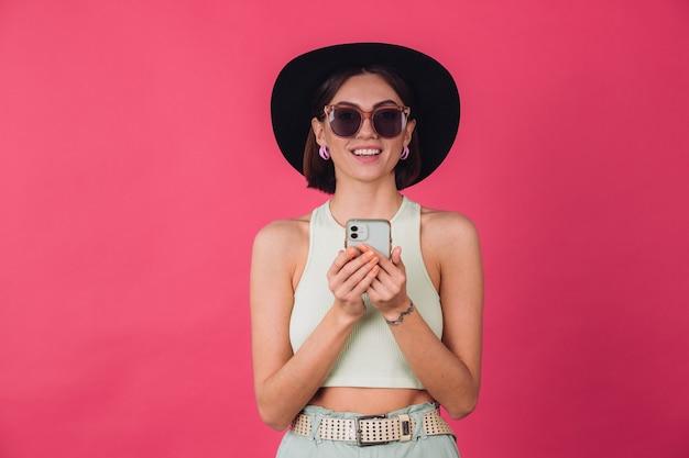 Stilvolle frau in hut und sonnenbrille auf rosa roter wand