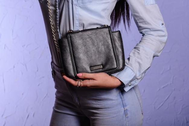 Stilvolle frau in jeans mit kleiner schwarzer handtaschenkupplung