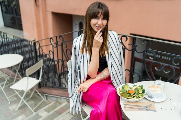 Stilvolle frau in lässigem sommeroutfit beim frühstück während der kaffeepause.