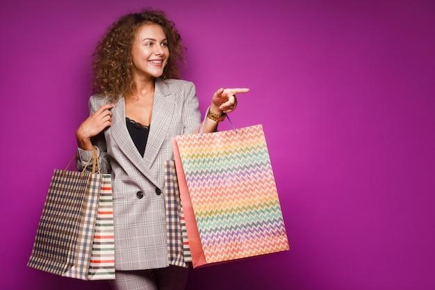 Stilvolle frau in modischer kleidung geht vom ladengeschäft auf violett