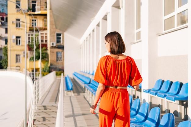 Stilvolle frau in orangefarbener kleidung bei sonnenuntergang am radwegstadion posiert