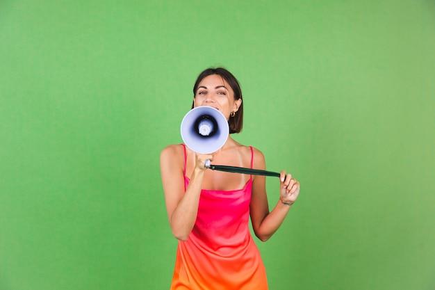Stilvolle frau in rosa seidenkleid auf grün, glücklich aufgeregt freudig fröhliches schreien im megaphon, isoliert