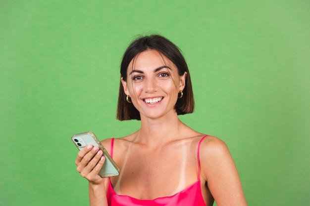 Stilvolle frau in rosa seidenkleid isoliert auf grün glücklich mit handy mit einem riesigen selbstbewussten lächeln
