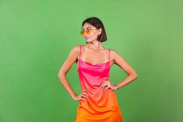 Stilvolle frau in rosa seidenkleid isoliert auf grünem posing, perfekte kurven, schlank, gebräunt
