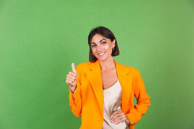 Stilvolle frau in seidenbeigem kleid und orangefarbenem oversized-blazer auf grün, positiv aufgeregt zeigt daumen hoch