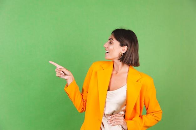 Stilvolle frau in seidenbeigem kleid und orangefarbenem oversized-blazer auf grünem, positiv aufgeregtem zeigefinger links