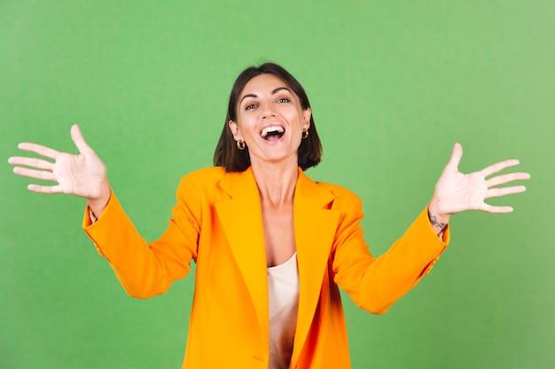 Stilvolle frau in seidenbeigem kleid und orangefarbenem übergroßem blazer auf grün, schreiend aufgeregt, die hände hebenraising