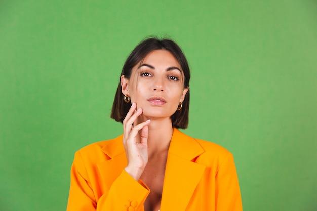 Stilvolle frau in seidenbeigem kleid und orangefarbenem übergroßem blazer auf grünem, positivem emotionenlächeln