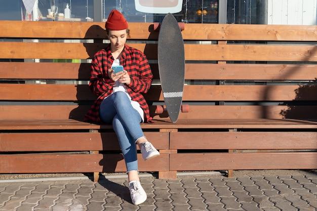 Stilvolle frau in trendigem rotem hut verwenden smartphone-chat im freien senden nachricht neben longboard sitzen