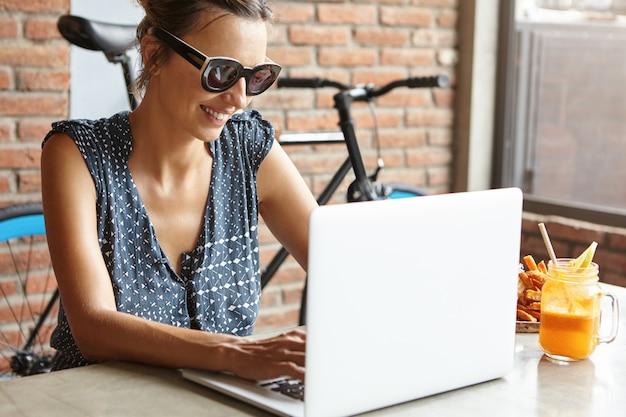Stilvolle frau mit charmantem lächeln sitzt vor offenem laptop und genießt online-kommunikation