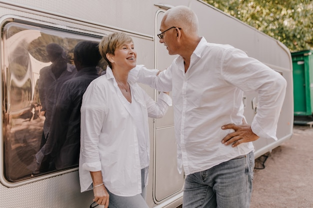 Stilvolle frau mit den blonden haaren in der weißen bluse und in den jeans lacht und betrachtet den grauhaarigen mann im hellen hemd im freien.
