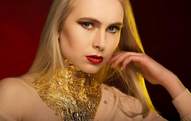 Stilvolle frau mit hellem make-up und goldfolie am hals