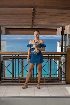 Stilvolle frau mit hund auf hotelterrasse
