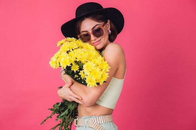 Stilvolle frau mit hut und sonnenbrille, die einen großen strauß gelber astern umarmt, frühlingsstimmung, ruhig lächelnder isolierter raum