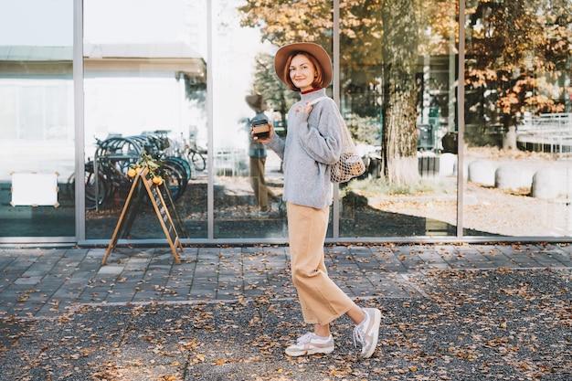 Stilvolle frau mit kauf in wiederverwendbarer netztasche aus baumwolle auf der schaufensterfront des zero-waste-ladens