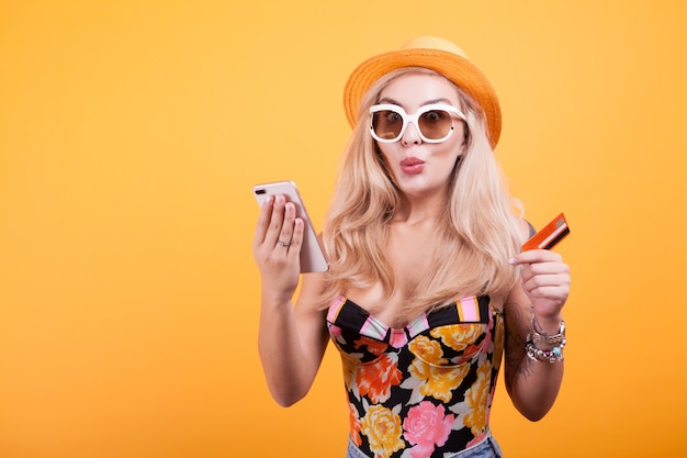 Stilvolle frau mit kreditkarte und telefon im studio über gelbem hintergrund