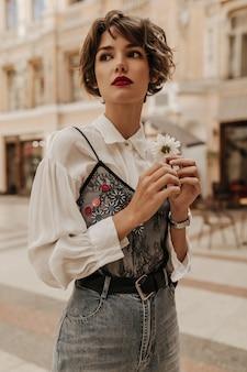 Stilvolle frau mit kurzen haaren in jeans mit gürtel, der blume an straße hält. frau in der weißen bluse mit der schwarzen spitze, die in der stadt aufwirft.